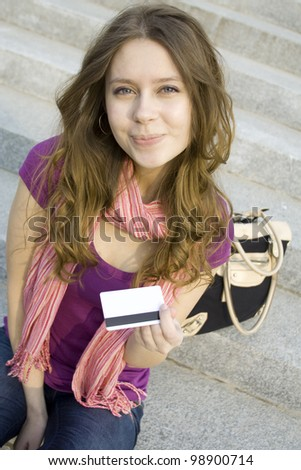 Close-up attractive woman holds in her hand a plastic card for purchases