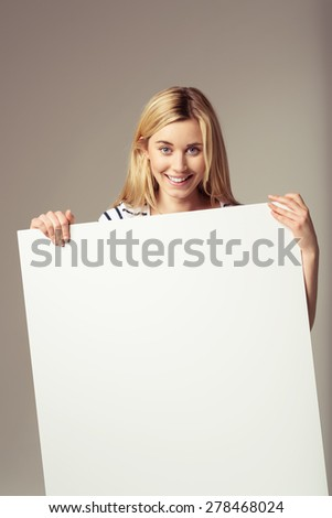 Close up Attractive Young Blond Woman Showing Blank Signboard at the Camera, Emphasizing Copy Space, on a Brown Background. - stock photo