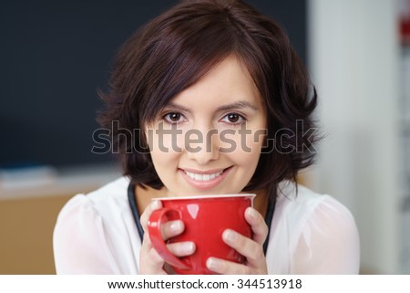 Close up Attractive Young Office Woman Holding a Red Cup of Hot Drink Using Two Hands and Smiling at the Camera - stock photo