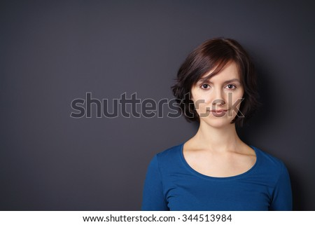 Close up Attractive Young Slim Woman Looking at the Camera with Half Smile Face Against Gray Wall with Copy Space. - stock photo