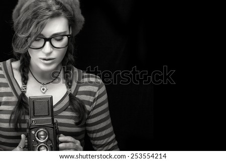 Close up Attractive Young Woman in Red Trendy Outfit Capturing Photo Using Vintage Camera. Monochrome Portrait Isolated on Black Background with Copy Space for Text. - stock photo