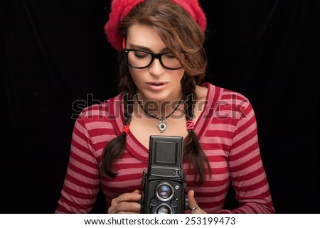 Close up Attractive Young Woman in Red Trendy Outfit Capturing Photo Using Vintage Camera. Isolated on Black Background with Copy Space