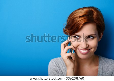 Close up Attractive Young Woman Listening to Someone Talking Through Phone Against Blue Wall Background with Copy Space. - stock photo