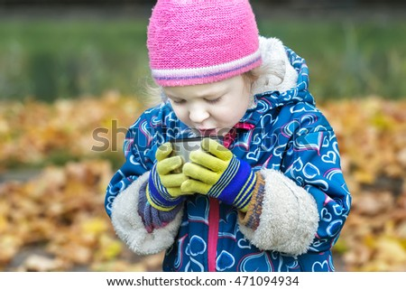 Close-up autumn portrait of little girl drinking hot beverage from stainless thermos flask cup