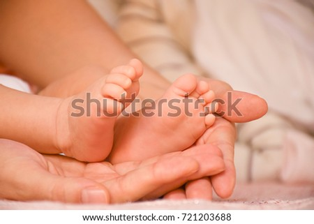 Close-up baby feet in mother hands. Tiny legs of newborn child. First days of life. Mom and her baby. Image of maternity and family.