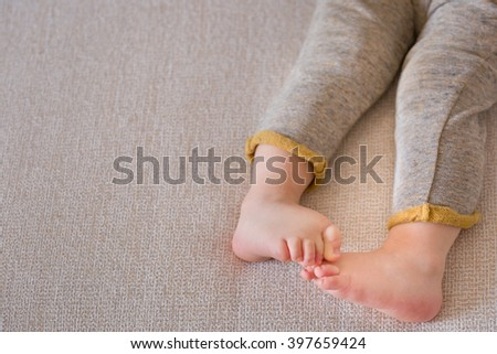 Close up baby legs. Baby feet on the sofa. Barefoot. - stock photo