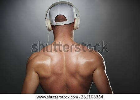 Close up Back View of a Shirtless Muscular Man with White Cap, Listening to Music Using Headphones, on a Gray Gradient Background. - stock photo