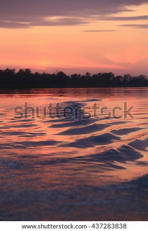 close-up background texture blurred image of waves on the river at sunset