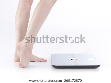 Close up Bare Female Feet and Legs Standing on the Floor Near a Smart Body Analyzer Technology for Measuring Weights, Isolated on White Background. - stock photo