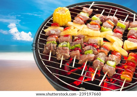 Close up bbq and corncob on a grilling pan on beach and blue sky   - stock photo