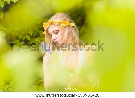 Close-up - beautiful makeup girl wearing white tunic and an antique jewels, green leaves around - stock photo