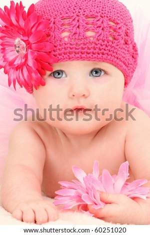 Close up beautiful 4 month old american baby girl in pink flower hat and tutu.
