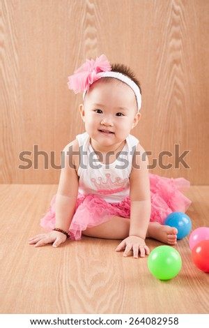 Close up beautiful 12 months old american baby girl in pink flower hat and tutu.