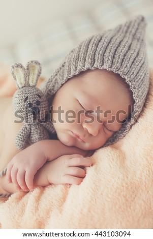 Close-up beautiful sleeping baby girl. Newborn baby girl, asleep on a blanket. A portrait of a beautiful, seven day old, newborn baby girl wearing a large, fabric rose headband. Closeup photo - stock photo