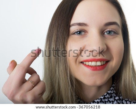 close-up beautiful sporty girl kissing middle finger. funny lifestyle portrait. concept  rebel