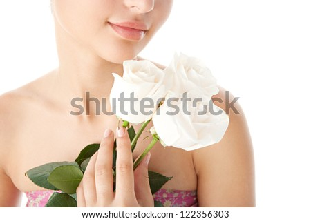 Close up beauty detail view of a young woman holding three perfectly shaped white roses, isolated on a white background.
