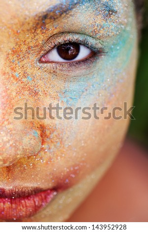 Close up beauty half portrait of a young girl face with voluptuous lips wearing golden yellow and blue and make up powder pigment and glitter covering her face, detail texture view.