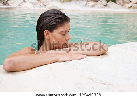 Close up beauty health spa portrait of a thoughtful natural young woman leaning on the stone edge of a clear spa swimming pool enjoying a holiday and relaxing outdoors. Travel and beauty lifestyle. - stock photo