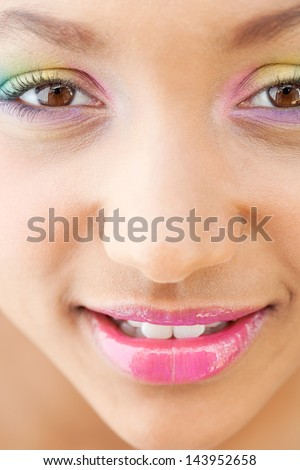 Close up beauty part portrait of a young girl face with voluptuous lips wearing a rainbow color eye shadow and smiling with glossy pink lipstick.