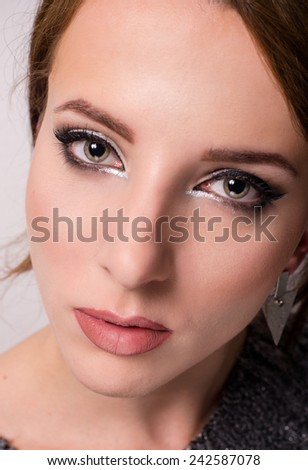 Close up beauty portrait of a lovely young grey eyed woman wearing trendy eye makeup looking into the lens with a serious expression - stock photo