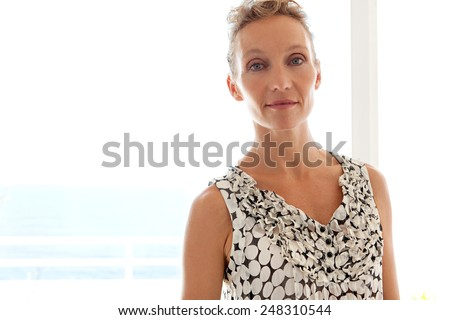 Close up beauty portrait of a mature professional working woman smiling at the camera while standing against a bright light window in a home office space, interior. Business and lifestyle at home. - stock photo