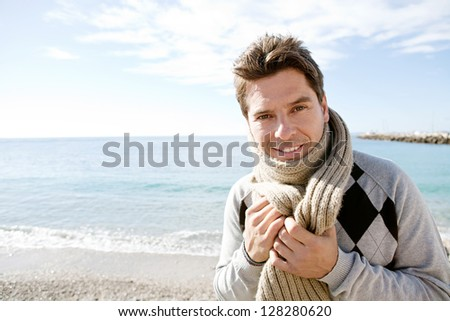 Close up beauty portrait of a smart man standing by the sea smiling and holding a wool scarf around his neck on a sunny winter day. - stock photo