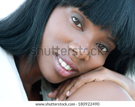 Close up beauty portrait of a young and attractive african american black woman with perfect skin, leaning on her knee and softly smiling turning to the camera. Health and beauty outdoors lifestyle.