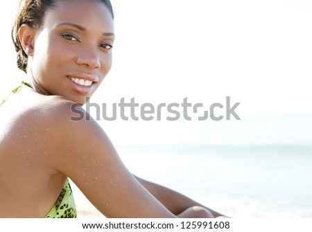 Close up beauty portrait of a young attractive african american woman sitting on a white sand beach while on vacation, relaxing. - stock photo