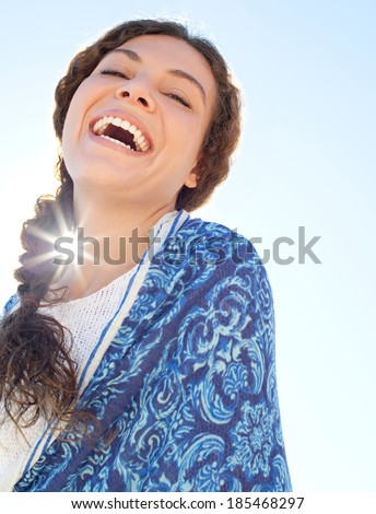 Close up beauty portrait of a young woman standing against a blue sky during a summer holiday wrapped in fabric with the sun rays filtering in while laughing. Beauty and healthy lifestyle, outdoors.