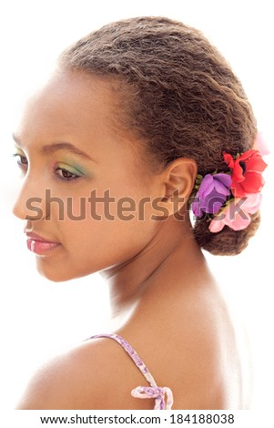 Close up beauty portrait of an attractive african american black young woman wearing make up and a floral hair detail, softly smiling against a white background. Beauty lifestyle.