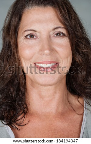 Close up beauty portrait of an attractive and healthy mature and senior professional woman with healthy skin and teeth, relaxing and smiling. Health and beauty lifestyle, interior.