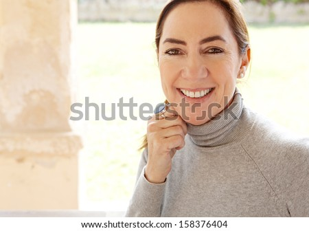 Close up beauty portrait of an attractive joyful and positive mature hispanic woman by a green grass garden during a sunny day at home, smiling and feeling positive. - stock photo