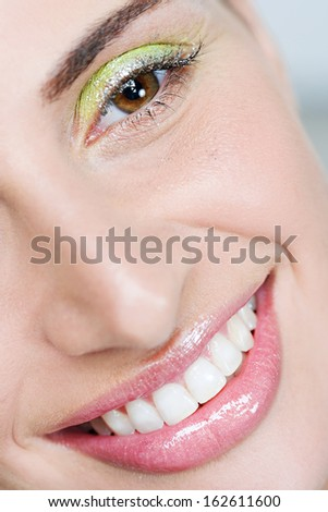 Close up beauty portrait of an attractive woman eye wearing fantasy colorful eyeshadow make up and glitter mascara for a party, smiling and looking at the camera, indoors.