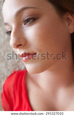 Close up beauty portrait of an attractive young woman laying on a bed, in a bright red dress, looking thoughtful and serene with beautiful eyes, home interior. Girl woman lifestyle, relaxing indoors. - stock photo