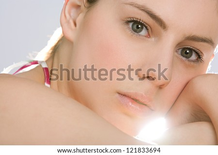 Close up beauty portrait of an attractive young woman looking at the camera with direct sun light filtering through her face with perfect skin. - stock photo