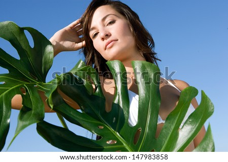 Close up beauty portrait of an attractive young woman wearing a bikini standing next to exotic green leaves against an intense blue sky during a sunny day, outdoors. - stock photo
