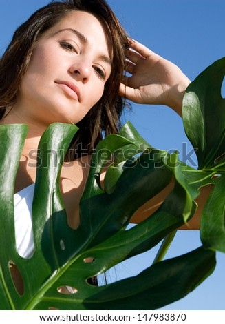 Close up beauty portrait of an attractive young woman wearing a bikini standing next to exotic green leaves against an intense blue sky during a sunny day, outdoors.