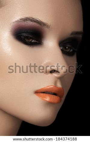 Close-up beauty portrait of attractive model face with bright make-up. Dark smoky eyes makeup, black ad purple eyeshadows, orange lips. Fashion witch style visage for Halloween  - stock photo