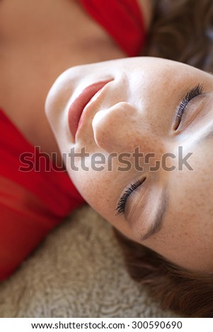 Close up beauty portrait of attractive young woman laying on a bed, wearing a bright red dress, sleeping with her eyes closed, home interior. Girl woman lifestyle and cosmetics, relaxing indoors. - stock photo