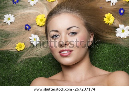 close-up beauty portrait of blonde smiling female with perfect skin and natural make-up posing lying on green grass with some colourful flowers in her long and smooth  hair  - stock photo