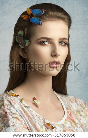 close-up beauty portrait of charming young girl with long brown hair and natural make-up posing with some colorful butterflies on head and shoulder  - stock photo