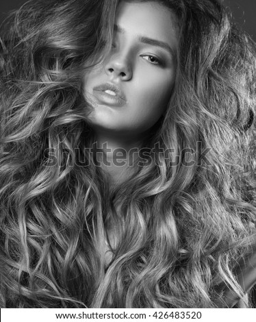 Close up beauty portrait of fashion model with long wavy volume hair.