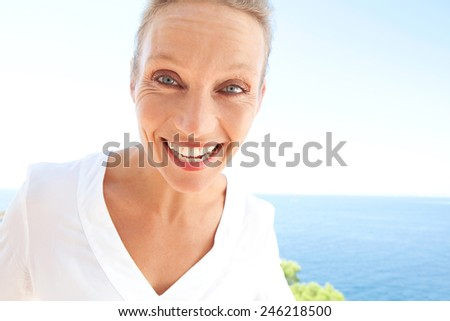 Close up beauty portrait of happy and joyful woman showing a fun and carefree expression of joy against a blue sky and sea background. Feelings and emotions in lifestyle. Gestures and expressions. - stock photo