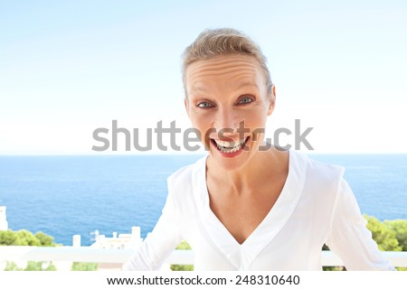 Close up beauty portrait of happy and joyful woman showing a fun and carefree expression of joy against a blue sky and sea background. Feelings and emotions in lifestyle living life, outdoors. - stock photo