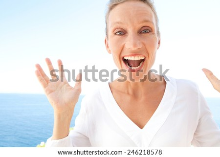 Close up beauty portrait of happy and joyful woman with a fun surprise and carefree expression of joy against blue sky and sea background. Feelings and emotions in lifestyle. Gestures and expressions. - stock photo