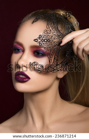 Close-up beauty portrait of pretty young blonde woman with evening make-up holding black party mask in her hand. - stock photo