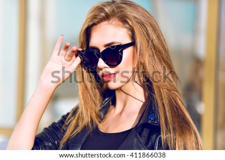 Close up beauty portrait of sexy stunning blonde woman, stylish black sunglasses, long hairs perfect skin, sunny day, black leather jacket. - stock photo