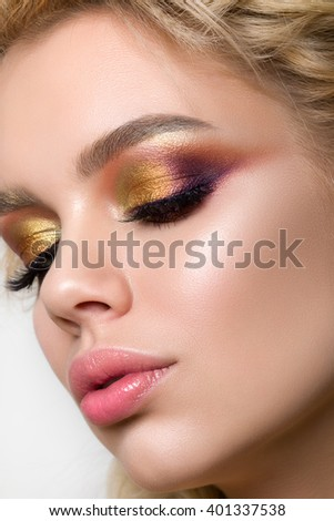 Close-up beauty portrait of young luxurious woman with modern creative make-up looking down. Multicolored smokey eyes and perfect brows - stock photo