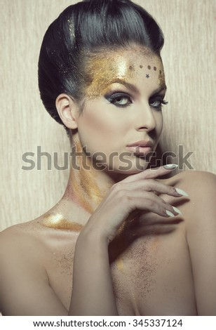 close-up beauty shoot of cute brunette woman with hair-style and creative glitter golden painted make-up, looking in camera and showing her perfect manicure  - stock photo