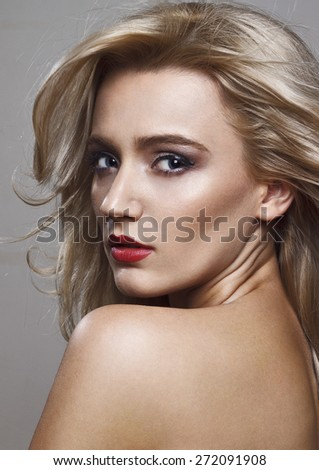 Close-up beauty shot of a beautiful young blonde women with the wind in the hair and sensuality in the eyes. - stock photo